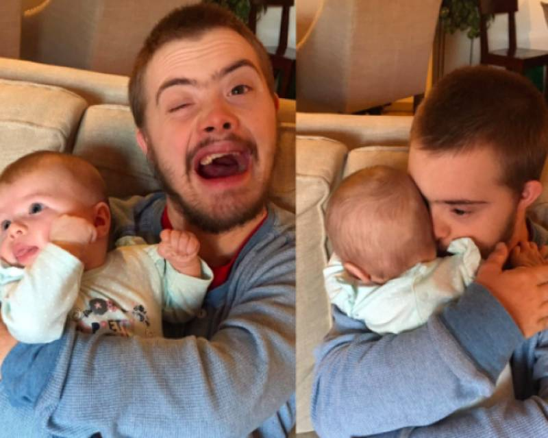 Photo of man with downs' syndrome holding a baby is a display of pure love